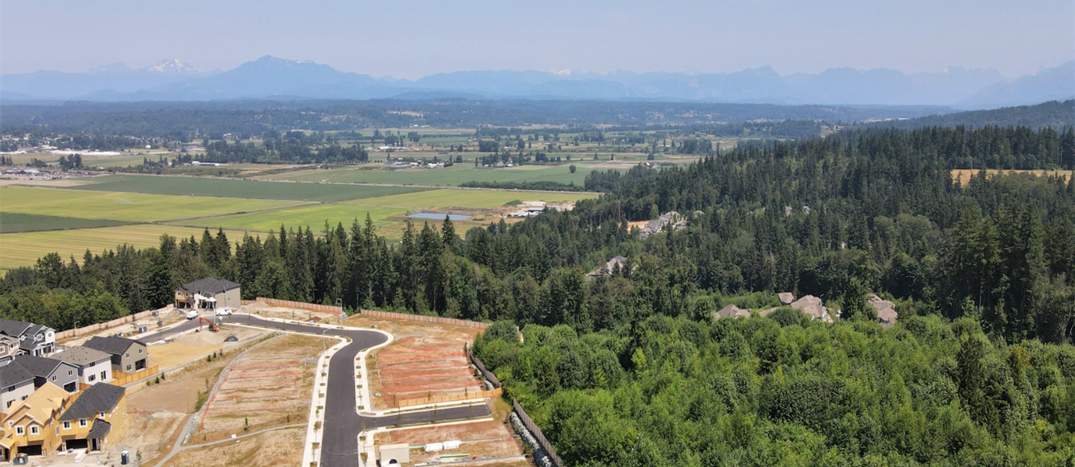 An aerial view of the community, which is surrounded by pine trees and features a mountainscape in the background