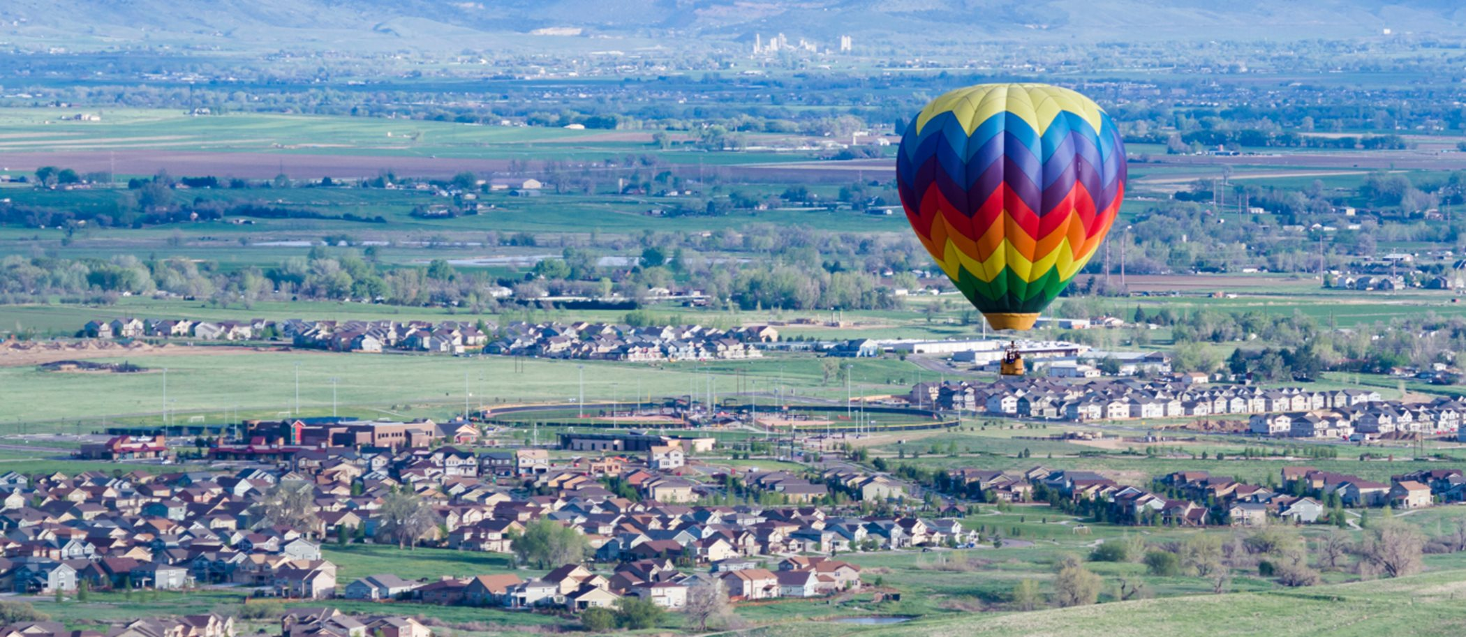 A hot air balloon flying over a town